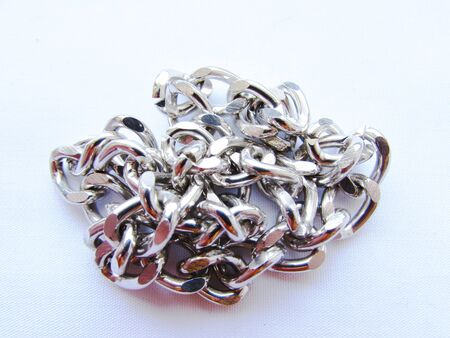 A long silver metal chain with large links lies crumpled on an white background isolated object.