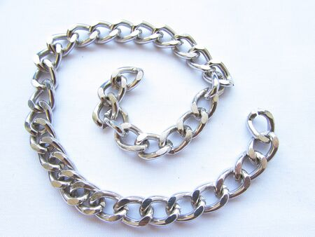 A long silver metal chain with links lies in a spiral isolated object on a white background. Imagens