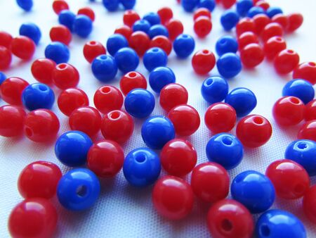 Bright red and deeply dark blue round beads for needlework are randomly scattered over a white background. Imagens