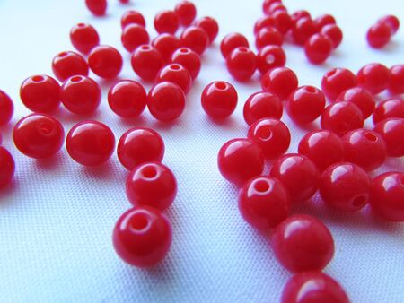 Bright deep red round beads for needlework are randomly scattered over a white background.