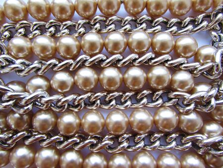 Beautiful mother-of-pearl light beige large beads on a thread and a silver metal chain lie on a white fabric background.