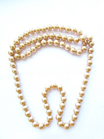 Beautiful mother-of-pearl light beige large beads on a tooth-shaped thread isolated object on a white background.