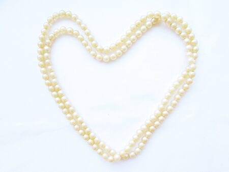 Gentle light small pearl long beads in the shape of a big heart on a white background.