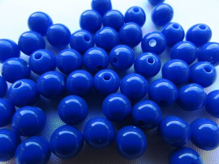 Brightly deep blue round beads for needlework are randomly scattered over a white background.