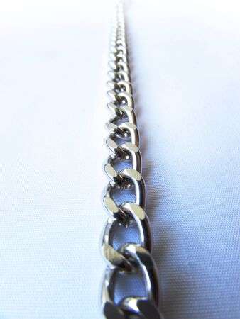 A long silver metal chain with links lies a vertically isolated object on a white background.