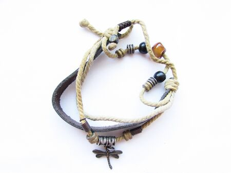 Cute handmade bracelet with a leather strap, a rope and beads isolated object on a white background. Imagens