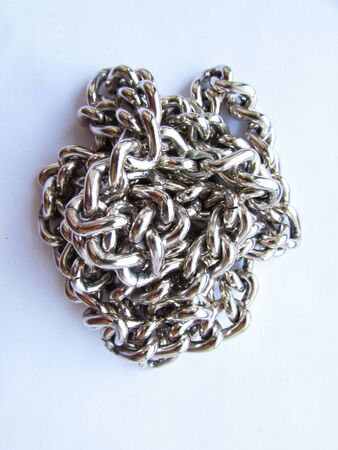 A long silver metal chain with links lies crumpled on an white background isolated object.