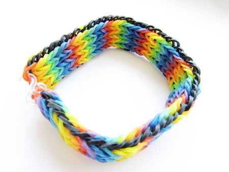 Childrens bright braided flat wide bracelet made of multi-colored small rubber bands isolated object on a white background.