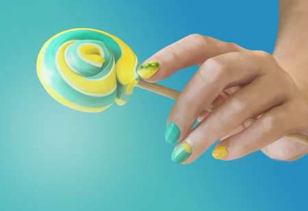 Sweet green yellow candy in her hands with a manicure on blue gradient background. Green yellow nail art. 免版税图像