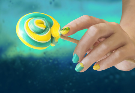 Sweet green yellow candy in her hands with a manicure on blur background. Green yellow nail art.