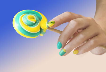 Sweet green yellow candy in her hands with a manicure on gradient background. Green yellow nail art.