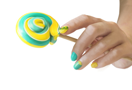 Sweet green yellow candy in her hands with a manicure on white background. Green yellow nail art. 免版税图像