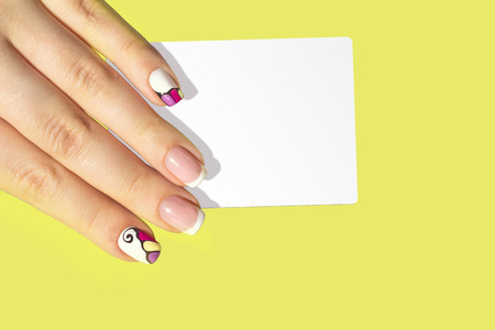 Female hand with french manicure holding card isolated on bright background 免版税图像