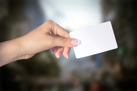 Female hand with french manicure holding card isolated on blur background