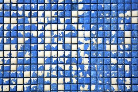 brownish: Peeling blue paint on white tiles