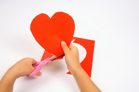 Baby use hand to cut paper to heart shape Stock Photo