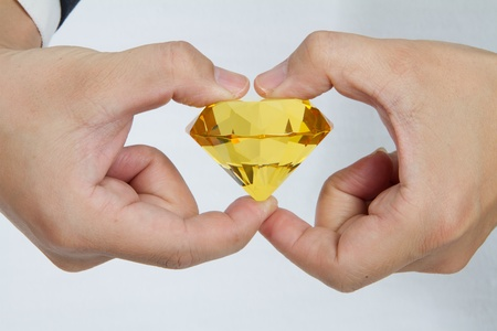 A business man holding with a huge yellow diamond photo