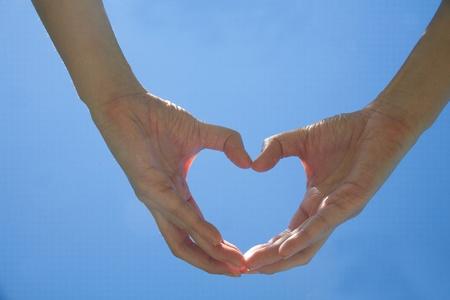 Hand make a heart  over the blue sky photo
