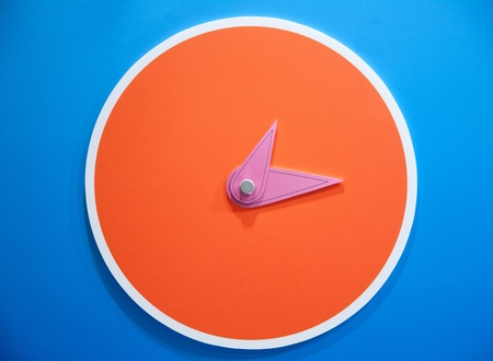 orange clock on blue wall photo