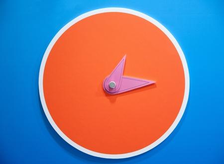 orange clock on blue wall photo