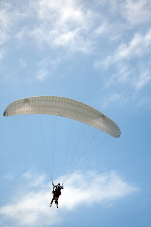 Paraglider against blue sky with coach photo