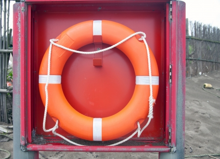 Red life buoy hung on box in the sand beach photo