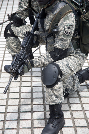disciplined: Soldiers lined up in camouflageSoldiers in army uniform line up holding guns