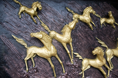 Golden Horses sculptures on the wall photo