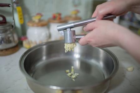 squeezing: Squeezing garlic Stock Photo