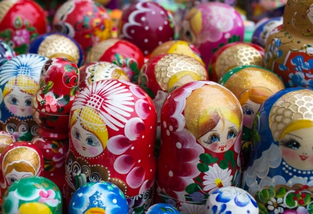 Unique wooden Russian Matryoshka dolls in different color shades. photo