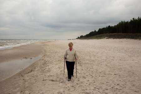 Women in middle aged recreation nordic walking on the beach in Debki, Poland. photo