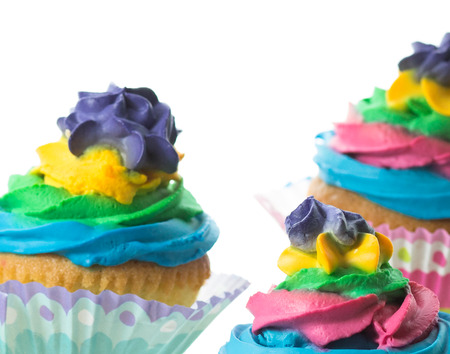 Tasty colored muffin cakes on a white background. photo