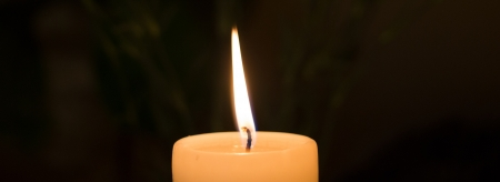 Burning candle symbolizes warmth, safety, and the memory of those who have gone. photo