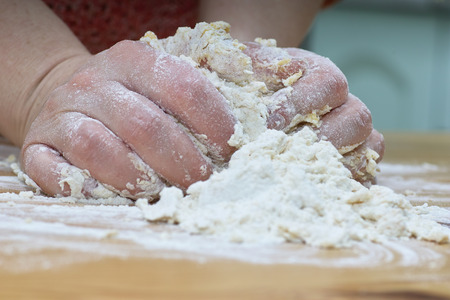 Preparing traditional Polish crunch cakes called Faworki or Chrust. Stock Photo