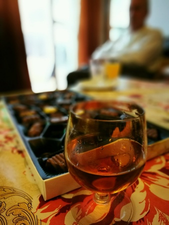 interior: Glass of brandy and box of delicious chocolates stuffed. Stock Photo
