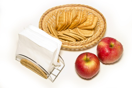Two red apples, napkin holders, wicker plate with cookies