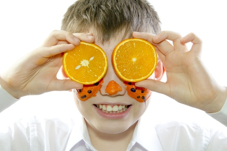 young boy holding orange slice in front of his eyes