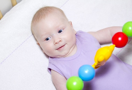 gray-eyed baby lies in bed and playing colored toys photo