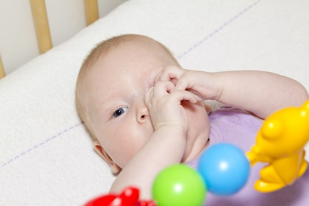 gray-eyed baby lies in bed and playing colored toys Stock Photo - 13163740