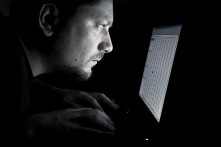 Serious man working on laptop in the dark photo