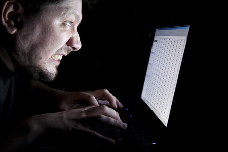 angry man working on laptop in the dark photo