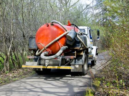 riool: oranje rioolwater septic tank op de vrachtwagen op het platteland Stockfoto