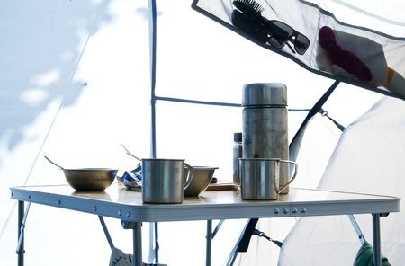 Table with tourist metal utensils inside camping tent