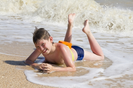 Boy lying on sand beach in the surf at sunny beach photo