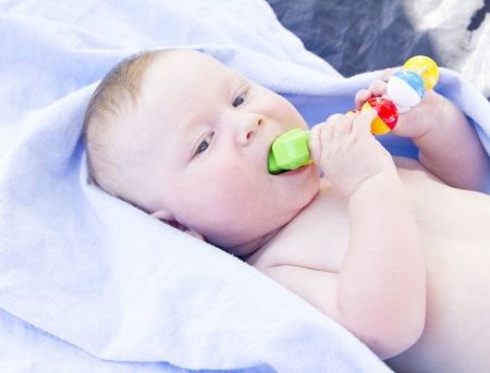 Six month old baby eating toy himself on blue fon Stock Photo - 14381350