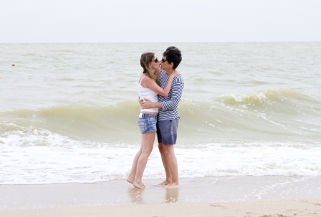 Happy couple enjoying together at the beach on ocean coast photo