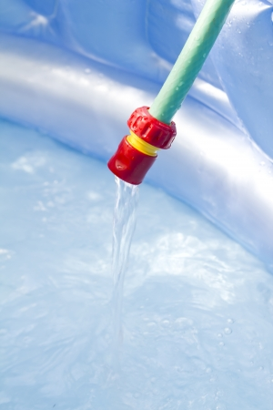 hoses: water flows from garden hose to childs swimming pool