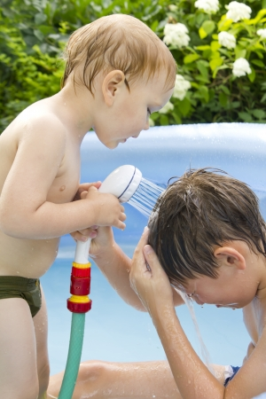 two boys in the small blue swimming pool outdoor