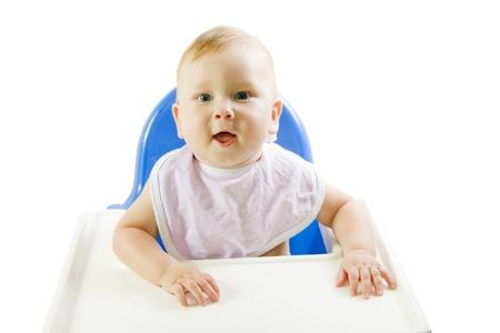 babero: Un joven de ojos azules, la alimentaci�n del ni�o de pur� de calabaza en una silla para la alimentaci�n