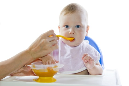 A young blue-eyed child feeding pumpkin puree in a chair for feeding